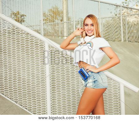 Beautiful young blond woman standing on the stairs in shorts, t-shirt with headphones and a cassette player. Warm sunny summer evening. Close up.