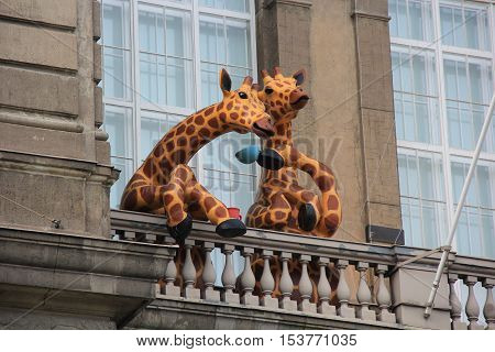 Two giant spotted giraffes drinking tea from big blue and red cups on an open balcony