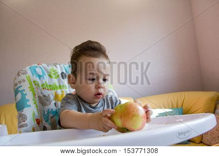 Adorable Indian baby boy eating apple over white background