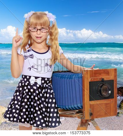 Adorable little blond girl wearing glasses and fancy dress polka dot advertises the old wooden camera.On the background of sea beach, warm sea and blue sky with clouds.