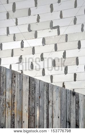 Texture of white wood planks. Wall of silicate blocks in the background. Selective focus.