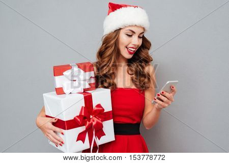Smiling girl with Christmas gifts looking at mobile phone. Santa's helper. Girl on dress and Santa's hat