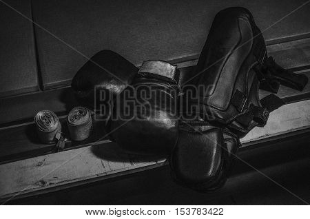 Equipment for Thai boxing pads knee pads bandages gloves lying on the bench in the sports hall