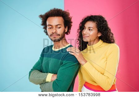 Beautiful african young woman talking to her updet offended boyfriend