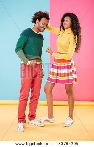 Angry african young woman pulling hair of her boyfriend and showing fist over colorful background