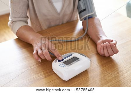 A asian women checking the blood pressure with a modern digital equipment