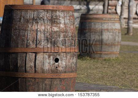 two wooden wine barrels kegs in a row outside cellar