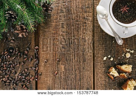 Cup of spiced tea and broken raisin cake on old brown wood with christmas decorations