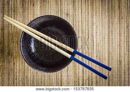 Chopsticks and rice or noodle bowl against a bamboo mat background focus on the chopsticks ideal for Asian or Oriental food subjects