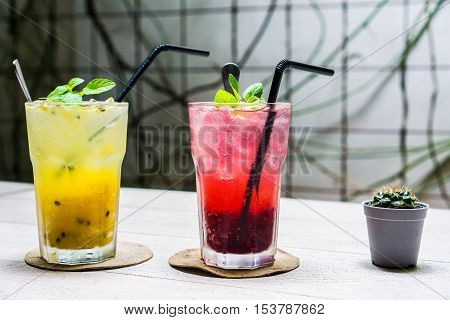 Colorful Sparkling Drink : Passion fruit-Mango Soda and Raspberry Soda to quench your thirst on the wooden table with small Cactus decoration
