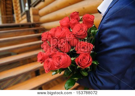 Man with a large bouquet of roses. Groom holding a bouquet of red roses.
