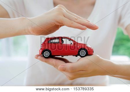 hands of a business woman holding a red toy car isolated