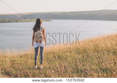 Back view of hipster young girl with backpack enjoying view on cliff. Tourist traveler on background view. Full body Mockup with copy space. filter effect