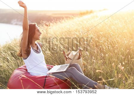 Euphoric woman searching job with a laptop in outdoors. Happy girl winner in meadow at sunrise with copy space