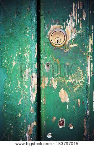 Keyhole lock on peeling painted green door