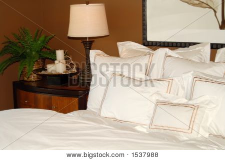Bed With White Bedspread And Nightstand