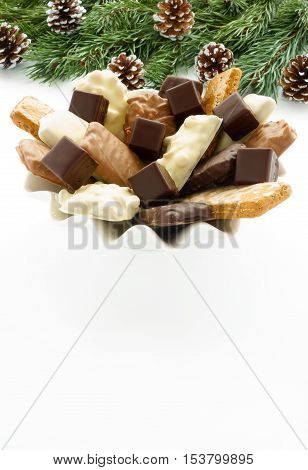 A large variety of Aachener Printen (German gingerbread speciality) and Dominosteine arranged on a white porcelain plate with fir tree twigs and pine cones on white background.
