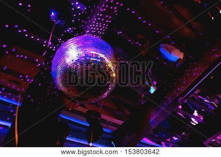 Shining bright purple mirror disco ball. Interesting device for discotheque dancing party with music in night club.