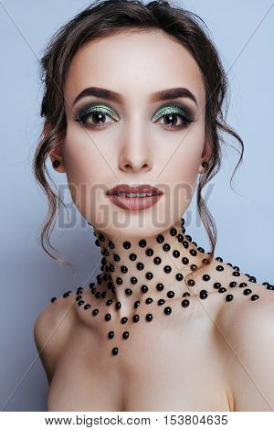 Elegant young lady with evening smart make up and beads on her neck. Make-up of woman eye with khaki eyeshadow. Beauty portrait of a girl model with make-upgreen eyes. Creative Professional makeup.