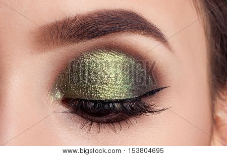 Make-up of woman eye with khaki eyeshadow. Beauty portrait of a girl model with make-upgreen eyes. Creative Professional makeup: green eye shadow. open the eyes. eyes closed