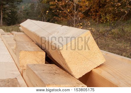 Wooden beams on the building. Fresh wooden beam, stacked at construction site.