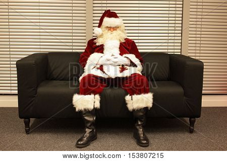 waiting for christmas job, santa claus sleeping on sofa in office