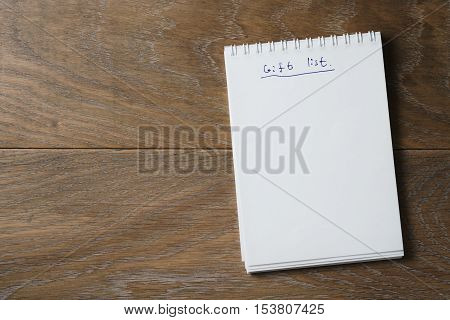gift list on notepad on wood table, blank notepad for your text