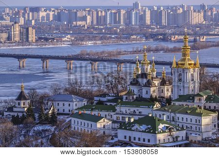 Panoramic view of Kiev Pechersk Lavra Monastery in winter. The Dnieper River, Paton Bridge, Church of the Nativity of the Virgin Mary, Bell tower at the Far Caves, 18th century