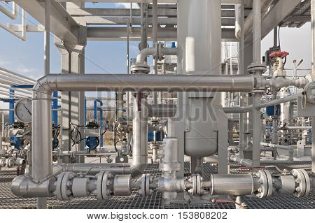 Details of a modern natural gas processing plant with pressure dials on gasworks pipes
