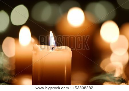 Burning candle with defocused candlelight background. Christmas or festive concept