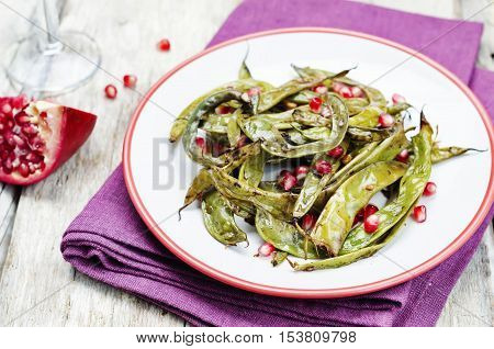 roasted snap green beans with Pomegranate on a white wood background