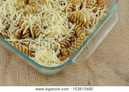 Casserole preparation of whole what rotini pasta and shredded mozzarella cheese