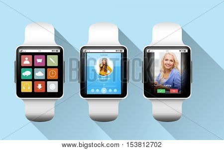 modern technology, object and media concept - close up of black smart watches with applications on screen over blue background