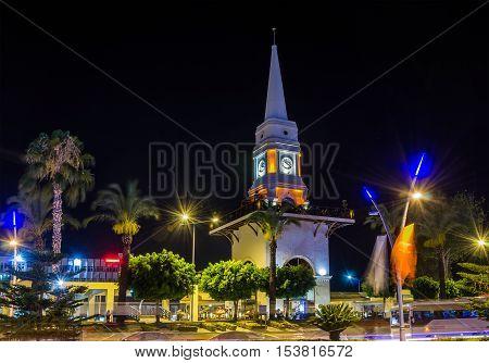 Illuminated central clock tower in Kemer Turkey. Kemer a seaside resort on the Mediterranean coast of Turkey Antalya Province. Night view.