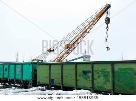 Freight train in loading under crane in an industrial area