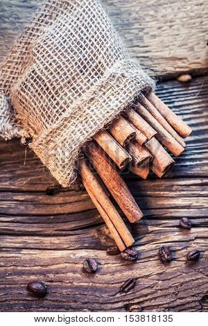 Cinnamon Sticks In A Burlap Sack On The Wooden Table