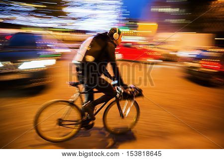 Paris France - October 19 2016: unidentified cycle courier in Paris at night shown in motion blur. Bicycle messengers are most often found in the central business districts of metropolitan areas