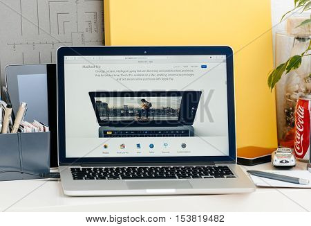 PARIS FRANCE - OCT 28 2016: Apple Computers website on new MacBook Pro Retina with OLED touch bar in a geek creative room showcasing new professional laptop - Touch ID is finnaly available on laptop