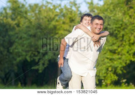 Family Values Concepts and Ideas. Happy Caucasian Family of Father and Son Piggybacking Outdoors. Against Nature Green Forest. Horizontal Image Orientation