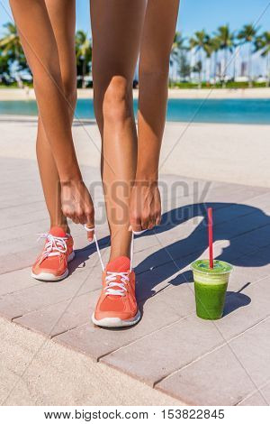 Running woman runner getting ready for workout by tying shoe laces of running shoes with green vegetable smoothie on beach boardwalk. Closeup of legs. Fitness and healthy lifestyle concept.