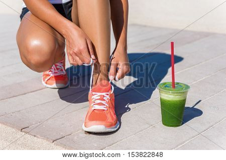 Running woman athlete runner getting ready for beach morning run by tying shoe laces of running shoes with green vegetable smoothie breakfast. Closeup on feet. Fitness and healthy lifestyle concept.