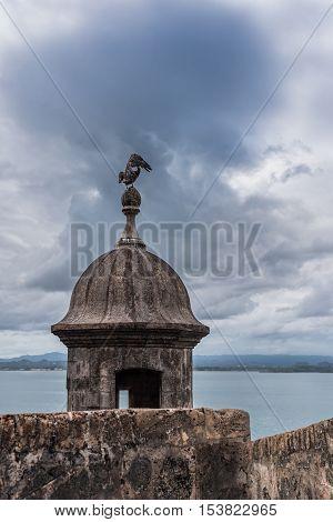 Castillo San Felipe del Morro tower with pelican on top. Angry stormy sky in San Juan Puerto Rico