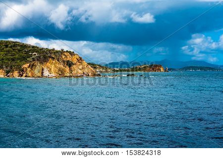 Rock formation in Caribbean Sea off the cost of St. Thomas in the Virgin Islands. Thunderstorm moving in on the right.