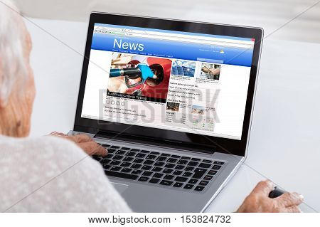 Close-up Of Senior Woman Reading News Online On Laptop At Home