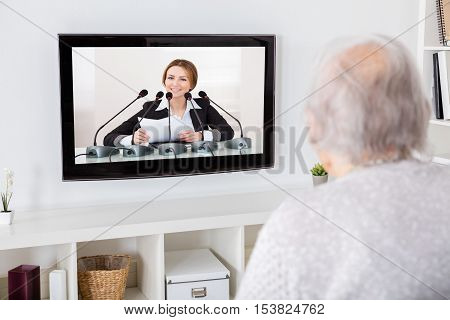 Close-up Of Grandmother Watching News On Television At Home