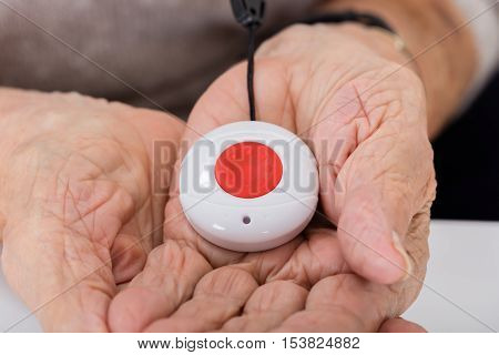 Close-up Of Senior Woman Holding Alarm Button For Emergency