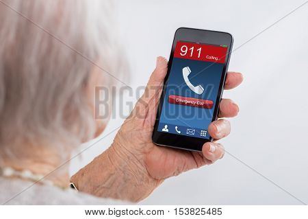 Close-up Of Senior Woman Dialing Emergency Call On Mobilephone At Home