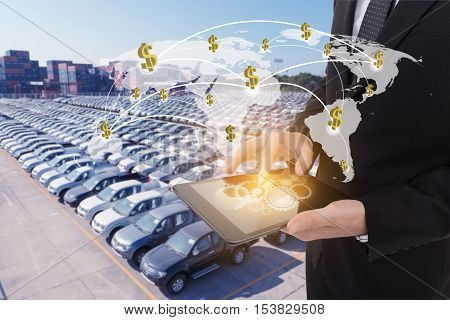 Image of businessman holding tablet Finance concept on Global network coverage world map Logistic Import Export automobile background (Elements of this image furnished by NASA)