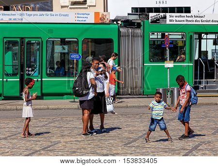 Basel, Switzerland - 27 August, 2016: people on Barfuesserplatz square green tram in the background. Basel is a city on the Rhine river in northwestern Switzerland, situated where the Swiss, German and French borders meet.