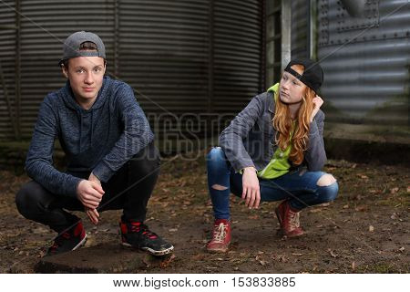 Two cool teenagers outdoor in front of metal background